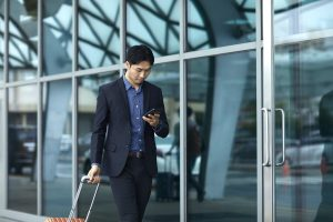 Businessman using phone while arriving at airport